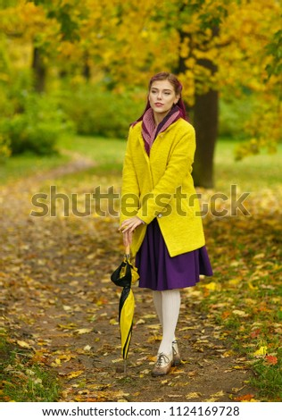 Portrait of an extravagant young woman with purple hair dressed in a yellow coat and purple skirt leaning on an umbrella on the path of an autumn park.Human facial expressions, emotions and feelings. #1124169728