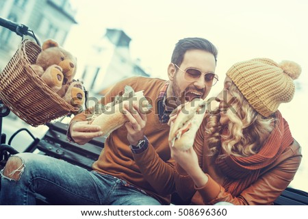 Portrait of an happy couple.They are laughing and eating sandwich and having a great time. #508696360