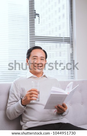 eeab94dbc8a4 Portrait of an happy mature man reading a book relaxed at home.  1044951730