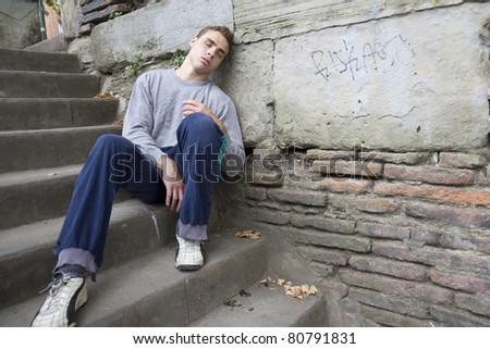 Portrait of an homeless man against a wall.