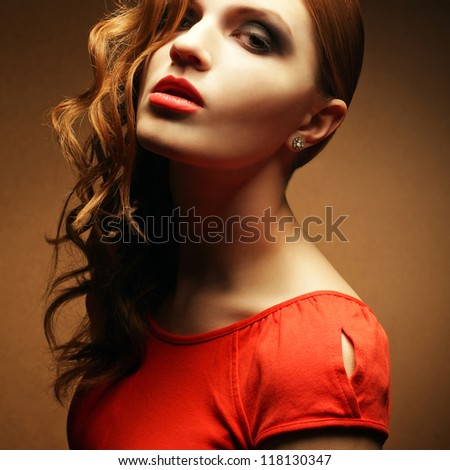 Portrait of an inaccessible beautiful ginger girl in orange dress with smoky eyes and diamond earring. Femme fatale in film noir. Studio shot