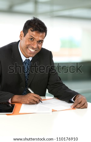 Portrait of an Indian business man working with his Digital Tablet.