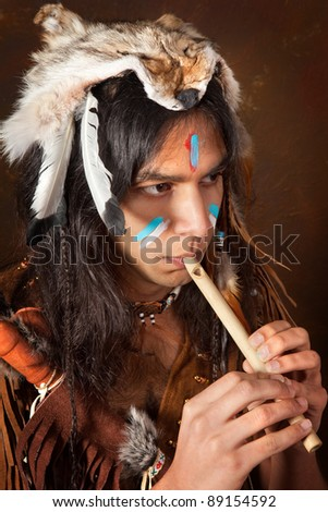 Portrait of an Indian in traditional costume wearing eagle feathers, coyote fur and beads