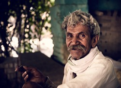 Portrait of an Indian old villager smiling while smoking with.