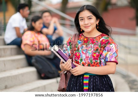Portrait of an indigenous college student with books in hands in the university building. Back to school.