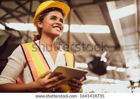 Portrait of an industrial woman worker standing with a big smile feeling proud and confident looking ahead in warm natural light, concept manufacturing industry, engineering worker profession.