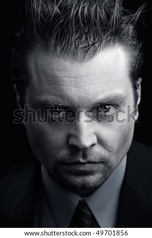 Portrait of  an  man with a heavy look on a dark background