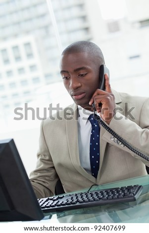 Portrait of an office worker making a phone call while using a computer