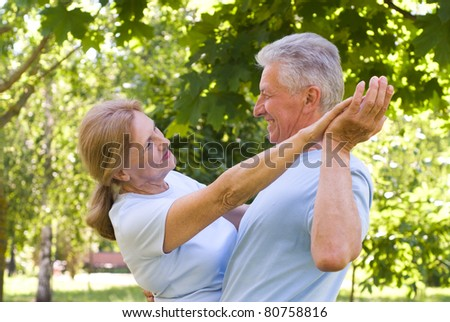 portrait of an old couple dancing at nature