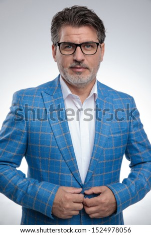 portrait of an old formal business man wearing a light blue suit and eyeglasses standing and with hands on his button while looking at camera happy against gray studio background Stock photo ©