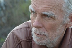 Portrait of an old gray haired unshaven man with a thoughtful look close up