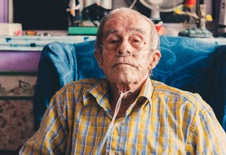 Portrait of an old man sitting at home with oxygen in his nose.
