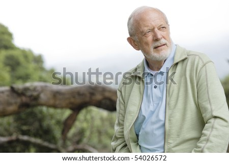 Portrait of an Old Man Sitting on a Treetrunk in Nature