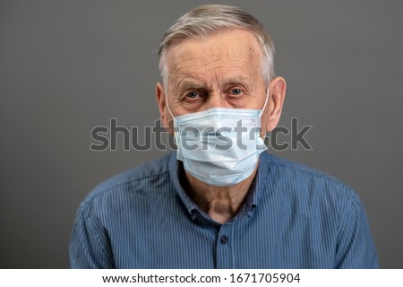 Portrait of an old man, 80 years old, in a medical mask. A concept of the danger of coronavirus for the elderly.