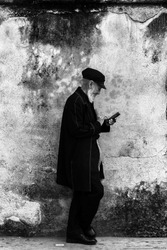 portrait of an old mexican man playing with his handy.