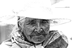 portrait of an old mexican woman with a white hat on a sunny day.