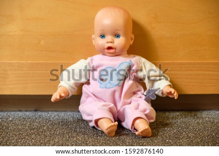 Portrait of an old used toy doll representing a caucasian baby sitting in front of a bright wall of a cabinet on the carpeted floor