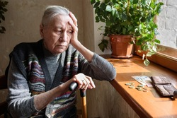 Portrait of an old woman counting money. The concept of old age, poverty, austerity.