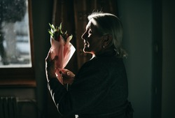 Portrait of an old woman, grandmother with a bouquet of tulips flowers at home, the sun, silhouette. International Women's Day, Mother's Day, honor to retirees. Happy life in old age, wrinkles.