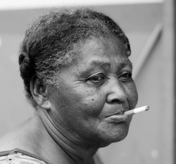 portrait of an old woman in black and white smoking cigar with a strange expression on her face that conveys sadness or bad thoughts