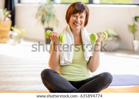 Portrait of an older woman in sportswear exercising with dumbbells indoors at home or gym #635894774