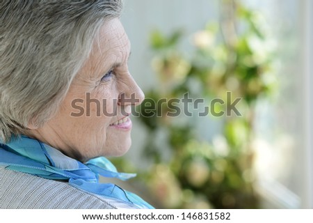 Portrait of an older woman with a blue neck scarf home