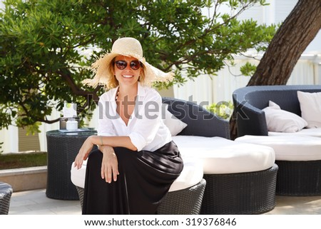 Portrait of an smiling middle age woman sitting in a beautiful garden at home and relaxing.