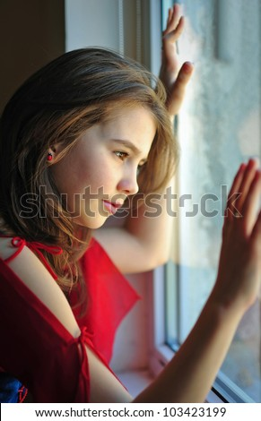 portrait of an unhappy teen girl looking out window