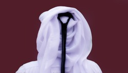 Portrait of an unknown Qatari man from behind in a traditional uniform isolated on maroon background