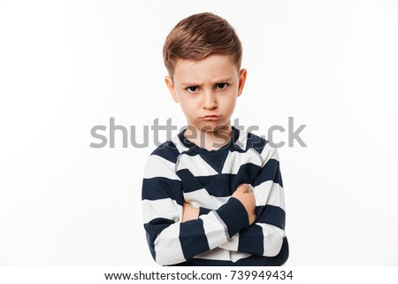 Portrait of an upset cute little kid standing with arms folded and looking at camera isolated over white background Stock foto ©