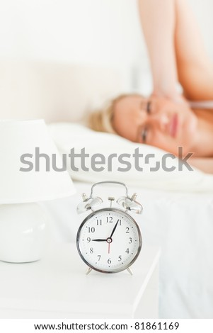 Portrait of an upset woman awake by her alarm clock with the camera focus on the clock