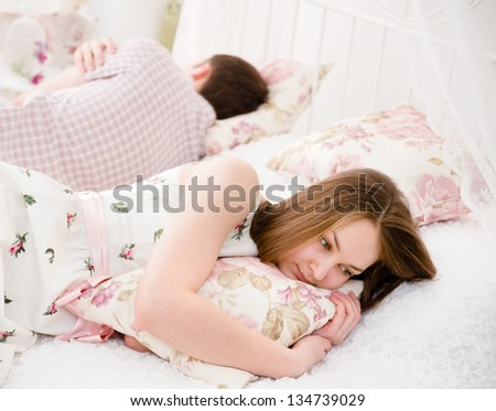Portrait of an upset young woman lying separately from husband on the bed
