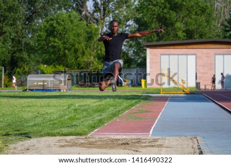 Portrait of an young african male athlete is performing a long jump on race track in athletics stadium in a sunny day.