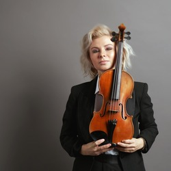 Portrait of an young beautiful caucasian blonde woman violinist wearing a black male suit holding a violin on the gray background
