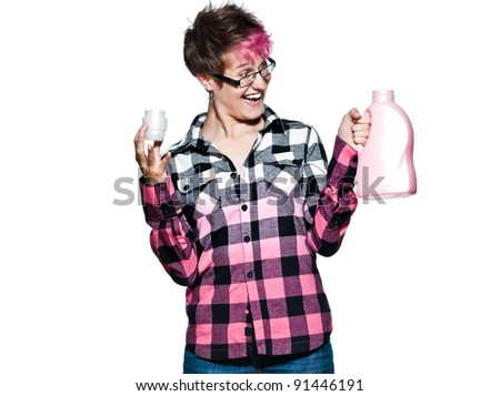 Portrait of an young cheerful woman looking at detergent bottle with pink dyed shirt in studio isolated on white background