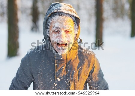 Portrait of an young frozen man with an open mouth while Jogging in a Blizzard in the woods. Face covered with snow.