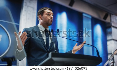 Portrait of an Young Organization Representative Speaking at Press Conference in Government Building. Press Officer Delivering a Speech at Summit. Minister Speaking at Congress Hearing.