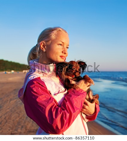 Portrait of an young woman at seaside with her dog