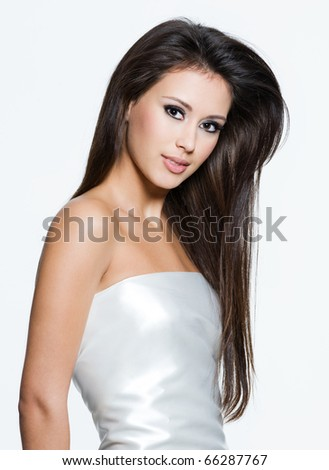 Portrait of an young woman with beautiful long brown hairs, posing isolated on white