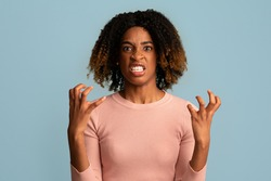 Portrait Of Angry African American Woman Looking AT Camera With Rage, Furious Young Black Female Raising Hands And Gritting Teeth While Standing Over Blue Background In Studio, Copy Space