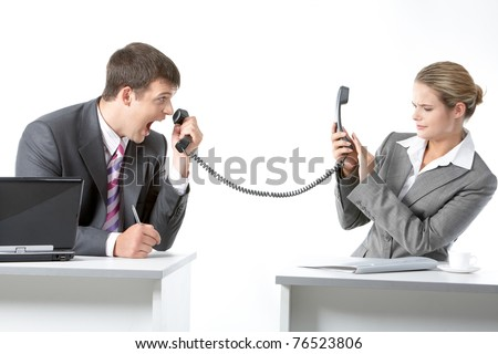 Portrait of angry boss shouting into telephone receiver at his secretary