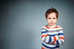 Portrait of angry little boy on blue background