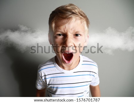 Portrait of angry little boy with steam coming out of ears on grey background