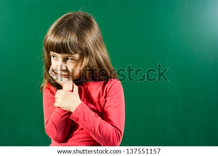 Portrait of angry little girl in front of blackboard,Angry little girl