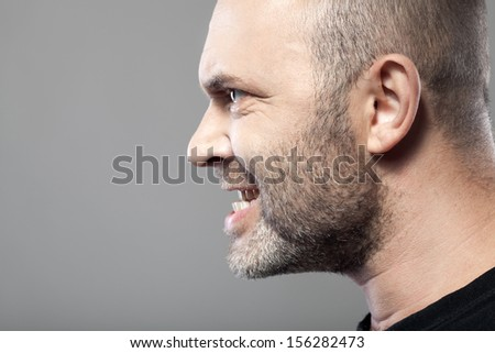 portrait of angry man isolated on gray background with copyspace