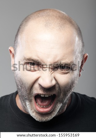 portrait of angry man screaming isolated on gray background