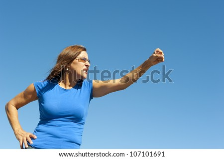 Portrait of angry mature woman, holding up one arm with fist, point towards right side, isolated with blue sky as background and copy space.