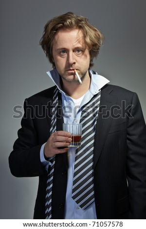 Portrait of angry young business man with cigarette and glass of whiskey.