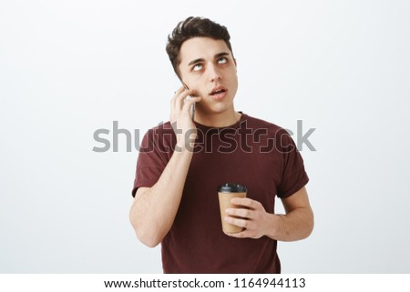 Portrait of annoyed pissed european guy in red t-shirt, holding cup of coffee, talking on smartphone and rolling eyelids from boredom and indifference, listening uninteresting story over gray wall #1164944113