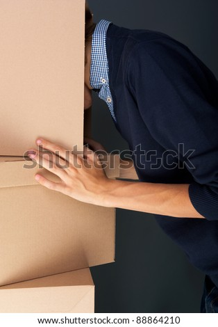 Portrait of anonymous young man with his head inside box